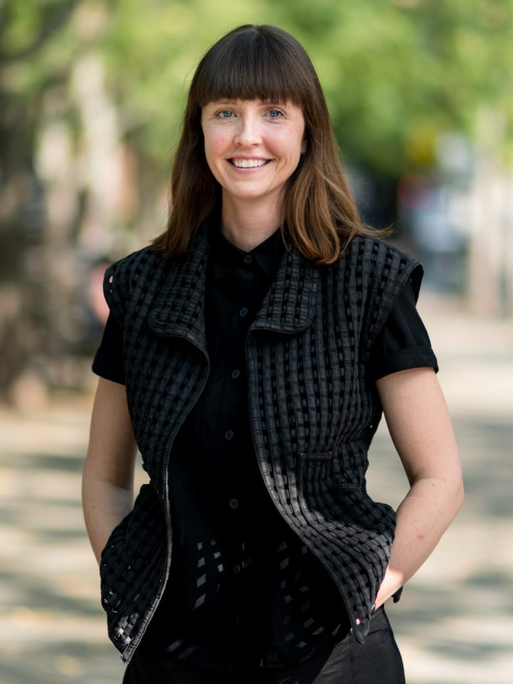 Anna Hermann Is An Architect On The Affordable Housing Team. She Has Brown Hair With Bangs And Stands Confidently With Her Hands In Her Pockets.