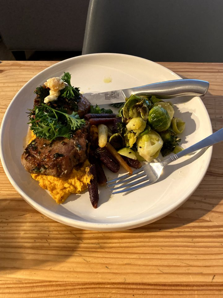 A Plate Full Of Brussel Sprouts And Pork Chops